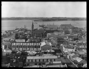 Looking north from St Matthews Church over the city and harbour to Stanley Point showing Hobson Street (extreme left), Hobson Wharf, Chapel Street (Federal Street, right) with St Patricks Cathedral (centre) and premises of Alexandra Hotel (centre) Aurora Hotel, J H Hannon and Charlie Tiy (right) in Albert Street - Sir George Grey Special Collection.